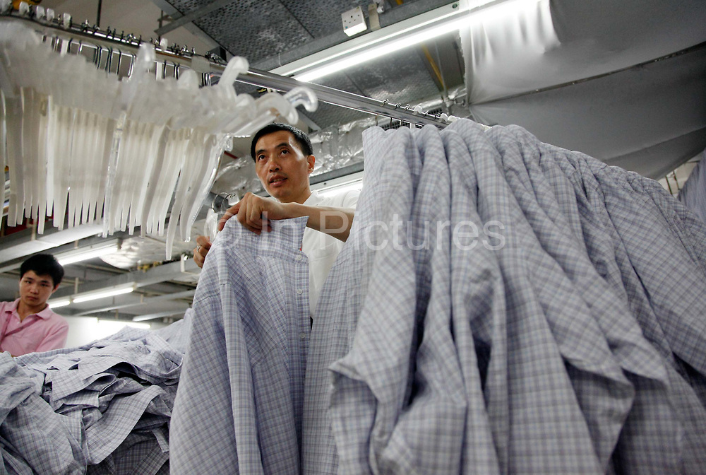 Employees put finished shirts onto clothe hangers at a Textile Alliance Apparel factory in Qingxi Township, Dongguan, Guangdong Province, China, on July 28, 2010. The factory supplies shirts and pants to major brands such as J Crew, Hugo Boss, Burberry, etc and produces over 300,000 shirts per day.