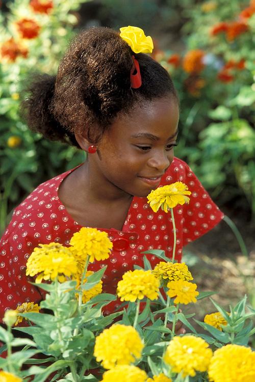 African-American girl smelling yellow flowers at school garden<br /> ©Bob Daemmrich/