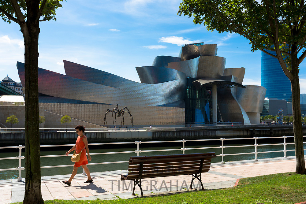 Woman walks past Architect Frank Gehry's Guggenheim Museum  across River Nervion at Bilbao, Basque country, Spain