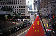 The Chinese flag hangs over Central, on the eve of the handover of sovereignty from Britain to China, on 30th June 1997, in Hong Kong, China.  Midnight signified the end of British rule, and the transfer of legal and financial authority back to China. Hong Kong was once known as fragrant harbour or Heung Keung because of the smell of transported sandal wood.