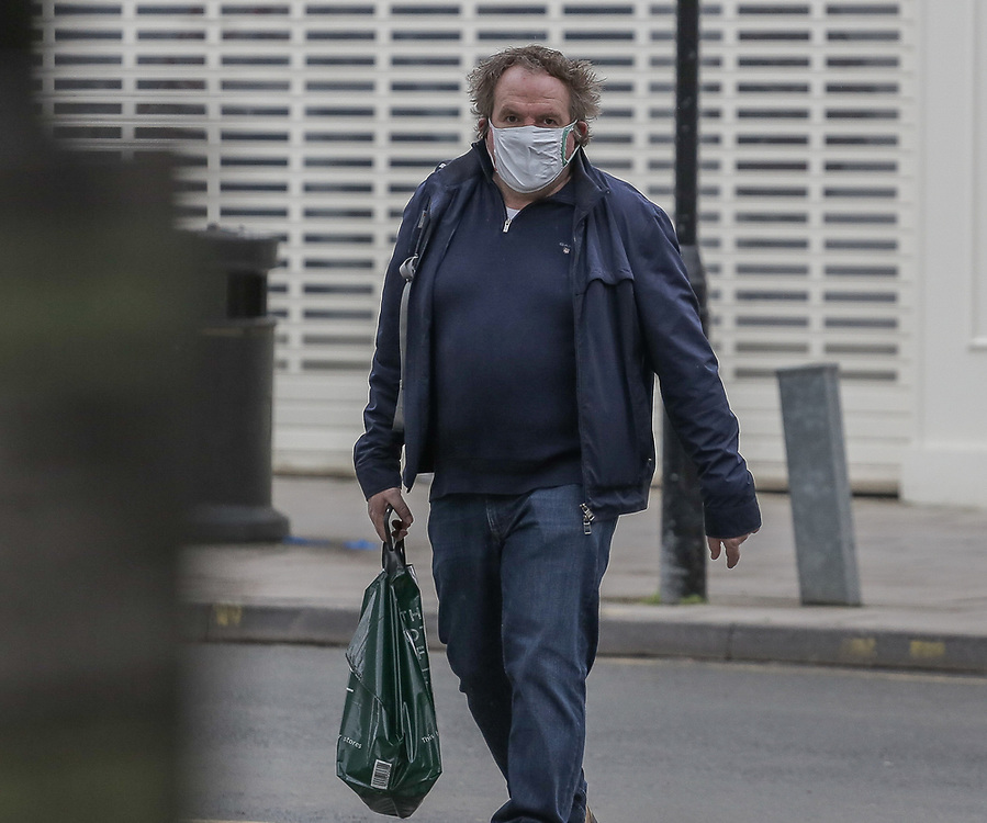 11th, March, 2021. Cheltenham, England. A member of the public walks through the town centre wearing a mask.