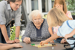 Senior woman with family enjoying board game in rest home, Bavaria, Germany
