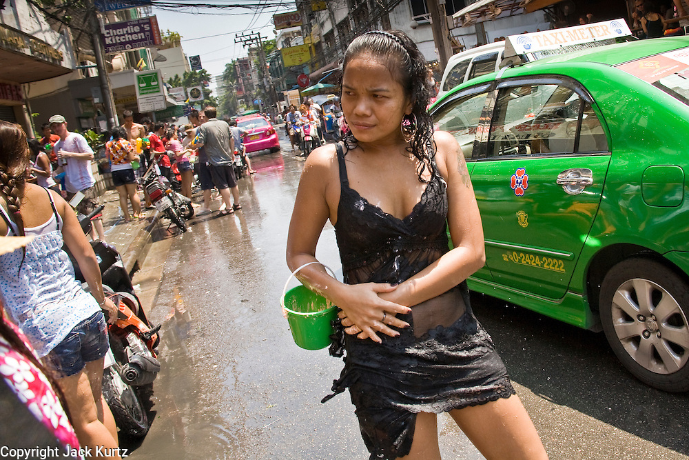 """Apr. 13, 2010 - Bangkok, Thailand: A Thai woman stands in the street after getting doused with water during Songkran festivities on a soi off of Sukhumvit Rd in Bangkok Tuesday. Songkran is the Thai New Year's holiday, celebrated from April 13 - 15. This year's official celebrations have been cancelled because of the Red Shirt protests but Thais are still marking the holiday. It's one of the most popular holidays in Thailand. Songkran originally was celebrated only in the north of Thailand, and was adapted from the Indian Holi festival. Except the Thais throw water instead of colored powder. The throwing of water originated as a way to pay respect to people, by capturing the water after it had been poured over the Buddhas for cleansing and then using this """"blessed"""" water to give good fortune to elders and family by gently pouring it on the shoulder. Among young people the holiday evolved to include dousing strangers with water to relieve the heat, since April is the hottest month in Thailand (temperatures can rise to over 100°F or 40°C on some days). This has further evolved into water fights and splashing water over people riding in vehicles. The water is meant as a symbol of washing all of the bad away and is sometimes filled with fragrant herbs when celebrated in the traditional manner. Photo by Jack Kurtz"""
