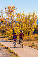 Couple riding bikes riding along the extensive bike trail system in Littleton, Colorado USA.