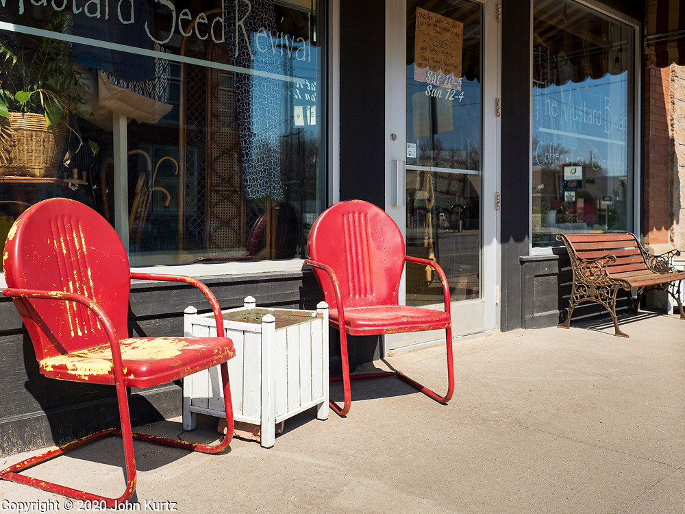 """26 APRIL 2020 - JEWELL, IOWA: Chairs and a table in front of a coffee shop in Jewell that is closed because of the COVID-19 pandemic. Jewell, a small community in central Iowa, became a food desert when the only grocery store in town closed in 2019. It served four communities within a 20 mile radius of Jewell. Some of the town's residents are trying to reopen the store, they are selling shares to form a co-op, and they hold regular fund raisers. Sunday, they served 550 """"grab and go"""" pork roast dinners. They charged a free will donation for the dinners. Despite the state wide restriction on large gatherings because of the COVID-19 pandemic, the event drew hundreds of people, who stayed in their cars while volunteers wearing masks collected money and brought food out to them. Organizers say they've raised about $180,000 of their $225,000 goal and they hope to open the new grocery store before summer.     PHOTO BY JACK KURTZ"""