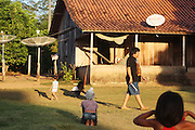 Chief Almir Narayamogo plays football with the children in the late afternoon. Sunset at a Surui village<br /><br />An Amazonian tribal chief Almir Narayamogo, leader of 1350 Surui Indians in Rondônia, near Cacaol, Brazil, with a $100,000 bounty on his head, is fighting for the survival of his people and their forest, and using the world's modern hi-tech tools; computers, smartphones, Google Earth and digital forestry surveillance. So far their fight has been very effective, leading to a most promising and novel result. In 2013, Almir Narayamogo, led his people to be the first and unique indigenous tribe in the world to manage their own REDD+ carbon project and sell carbon credits to the industrial world. By marketing the CO2 capacity of 250 000 hectares of their virgin forest, the forty year old Surui, has ensured the preservation, as well as a future of his community. <br /><br />In 2009, the four clans and 25 Surui villages voted in favour of a total moratorium on logging and the carbon credits project. <br /><br />They still face deforestation problems, such as illegal logging, and gold mining which causes pollution of their river systems