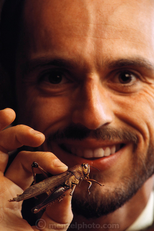 """Bruno Comby, author of """"Delicious Insects"""" (in French) holds a grasshopper before eating it. Comby lives and works in the Orkos Institute in the 17th century Chateau Montrame outside of Paris. His institute serves a raw diet  he calls """"instinctology"""" and describes as the Paleolithic nutritional practice by early human hunter-gatherer ancestors. Comby grows insects in cages for food. Image from the book project Man Eating Bugs: The Art and Science of Eating Insects."""