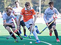 BLOEMENDAAL - HOCKEY -  Florian Fuchs (Bl'daal) met links Mark Rijkers (Oranje-Rood) en rechts Bram Huijbregts (Oranje-Rood)  tijdens de competitie hoofdklasse hockeywedstrijd Bloemendaal -ORANJE-ROOD (4-1)  COPYRIGHT KOEN SUYK