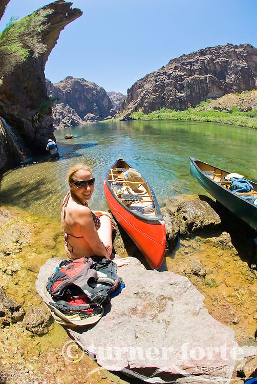 A woman enjoys the sun while on a paddle trip through The Black Canyon, Nevada.