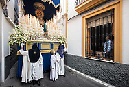 A woman salutes the Virgin Mary float passing in front of her house in a very narrow alley in the centre of Cordoba. Andalusia, Spain