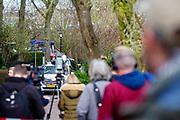 Pers en belangstellenden kjjken hoe de vliuchtauto wordt afgevoerd in Utrecht. Op de hoek is de vluchtauto aangetroffen van de mogelijke dader van de schietpartij in de tram.