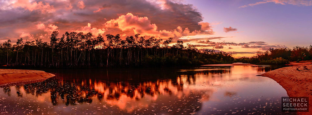Sunset over the mouth of a tidal creek at Yorkey's Knob Beach, with reflections of mangroves in the still water.<br /> <br /> Limited Edition of 125