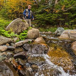 A man fly fishing in fall on Nash Stream in Reddington Township, Maine. High Peaks Region.