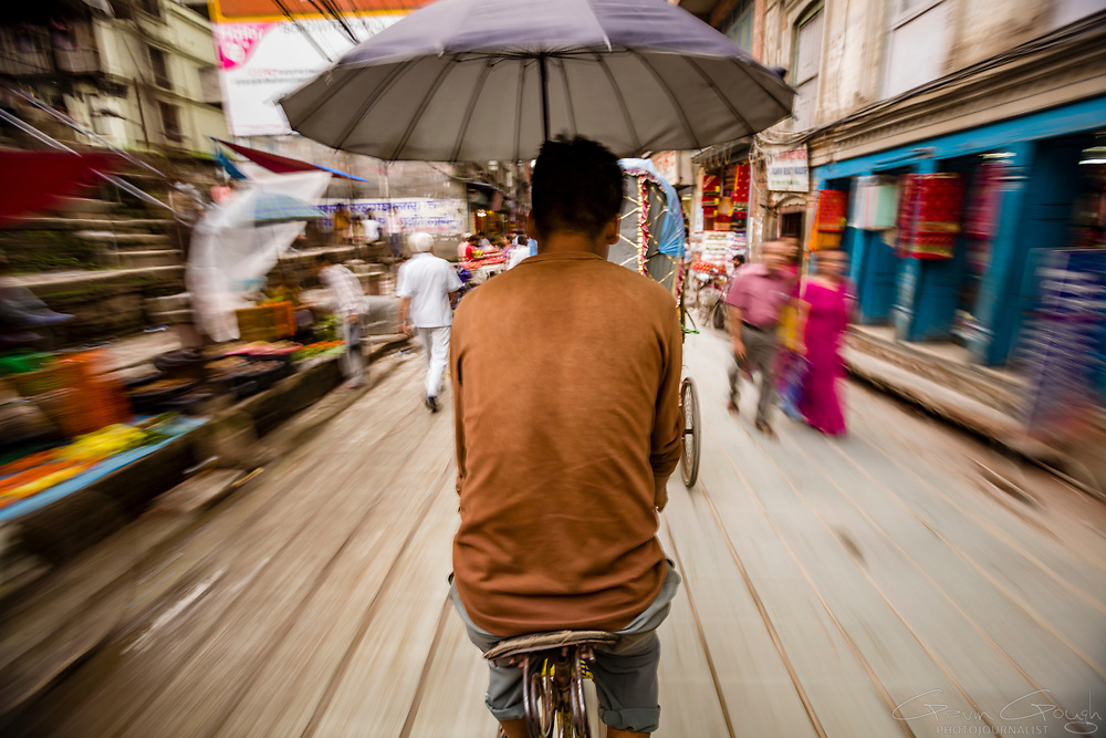 Rear view of a rickshaw driver beneath an umbrella cycling a passenger through the market, Durbar Square, Kathmandu, Nepal