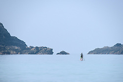 A paddle boarder on a misty, hazy day at Fistral in Newquay, Cornwall.