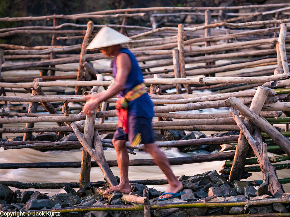19 JUNE 2016 - DON KHONE, CHAMPASAK, LAOS: A fisherman walks along the side of one of his fish traps at Khon Pa Soi Waterfalls, on the east side of Don Khon. It's the smaller of the two waterfalls in Don Khon. Fishermen have constructed an elaborate system of rope bridges over the falls they use to get to the fish traps they set. Fishermen in the area are contending with lower yields and smaller fish, threatening their way of life. The Mekong River is one of the most biodiverse and productive rivers on Earth. It is a global hotspot for freshwater fishes: over 1,000 species have been recorded there, second only to the Amazon. The Mekong River is also the most productive inland fishery in the world. The total harvest of fish from the Mekong is approximately 2.5 million metric tons per year. By some estimates the harvest in the Tonle Sap (in Cambodia) had doubled from 1940 to 1995, but the number of people fishing the in the lake has quadrupled, so the harvest per person is cut in half. There is evidence of over fishing in the Mekong - populations of large fish have shrunk and fishermen are bringing in smaller and smaller fish.     PHOTO BY JACK KURTZ