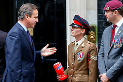 © Licensed to London News Pictures. 22/10/2015. London, UK. Prime Minister David Cameron buys a Royal British Legion poppy and meets current and former servicemen and women in Downing Street, London on Thursday, 22 October 2015. Photo credit: Tolga Akmen/LNP