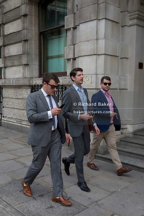Casually-dressed young successful businessmen, each with large cigars, walk along Conhill, a City of London street, on 11th August, 2017, in London, England.