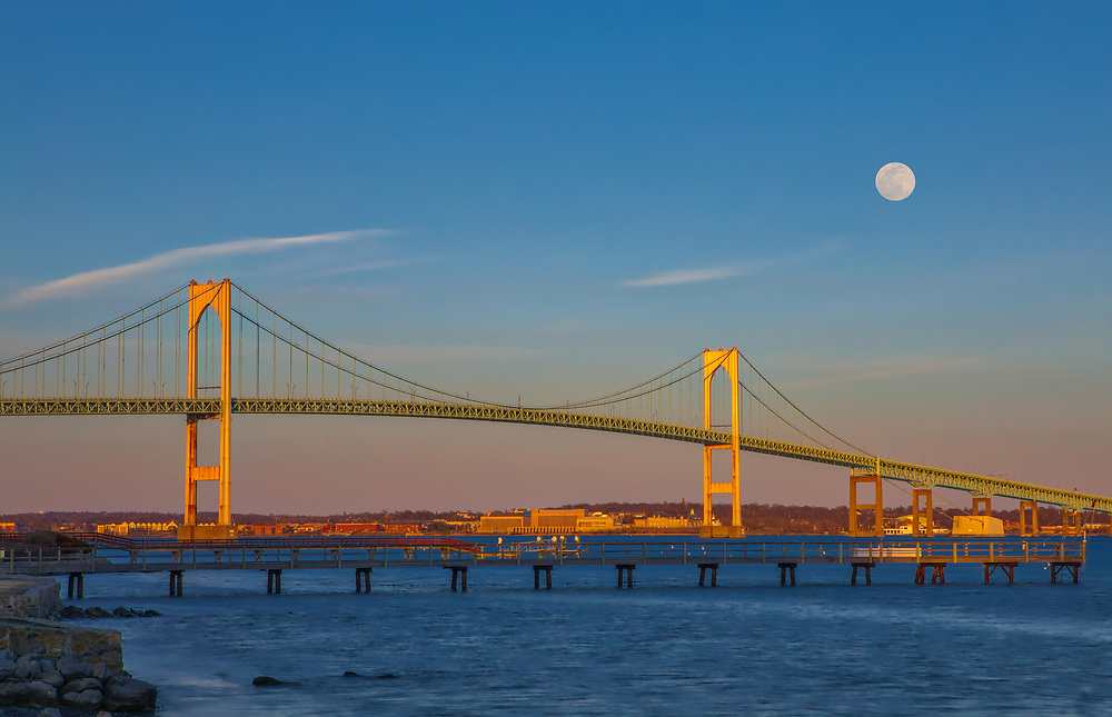 Coastal Rhode Island seascape and full moon photography over the Claiborne Pell Newport Bridge that spans Narragansett Bay connecting the City of Newport on Aquidneck Island and the Town of Jamestown on Conanicut Island. Rhode Island has become an inspiration and is a heaven for macro, seascape, and landscape photography that makes for great wall art. Especially sunrise, sunset and the light of the golden hours paint the sky in beautiful colors and bring out the beauty of the Ocean State as it did during this full moon rise.<br /> <br /> Rhode Island full moon photographs of the Claiborne Pell Newport Bridge are available for image licensing and as museum quality photography prints, canvas prints, acrylic prints, wood prints or metal prints. Wall art prints may be framed and matted to the individual liking and room decor needs:<br /> <br /> https://juergen-roth.pixels.com/featured/full-moon-over-the-rhode-island-newport-bridge-juergen-roth.html<br /> <br /> Good light and happy photo making! <br /> <br /> My best, <br /> <br /> Juergen