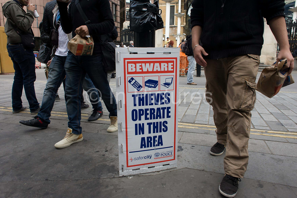 A warning by City police of thefts in the area around Liverpool Street station in the City of London. Pedestrians pass this temporary sign placed outside the mainline station, an area prone to petty thefts of wallets, laptops and the snatching of phones from travellers. The legs of anonymous men stride past the sign, ignoring the advice.