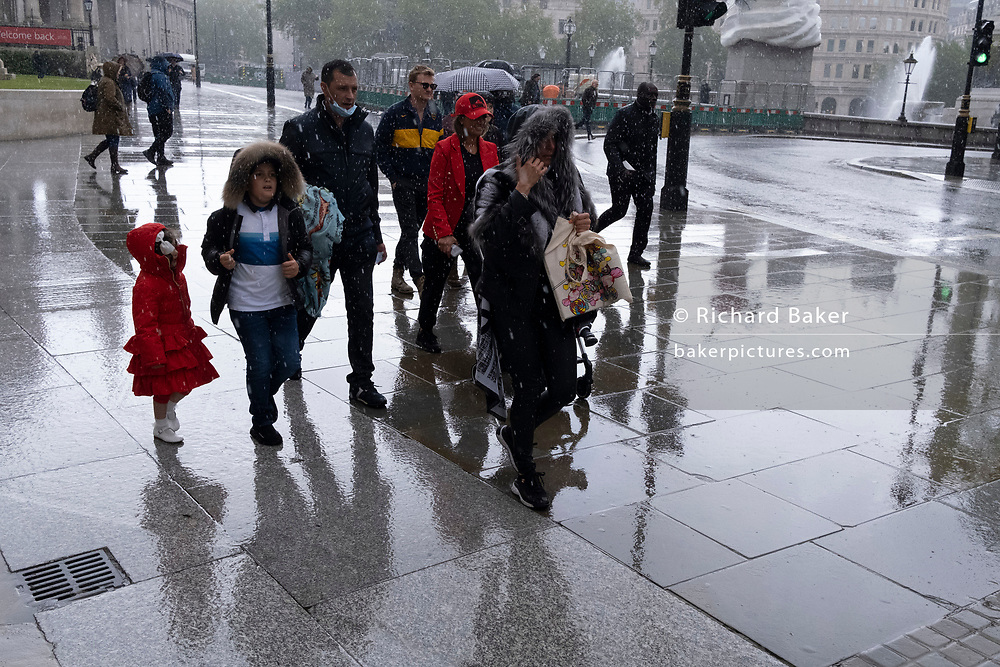 Wet Londoners walk along the paved area outside the National Gallery during seasonal Spring rainfall, on 24th May 2021, in London, England.