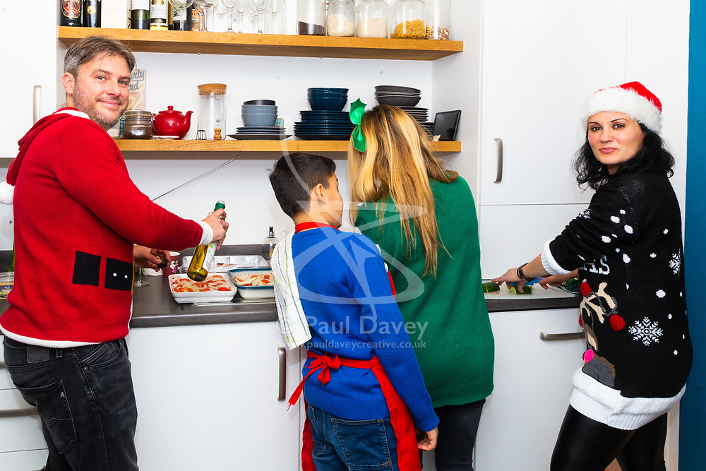 Left - right Lee, his son Charlie, Barby and Miriam prepare lunch in the kitchen. Brighton, December 16 2018.