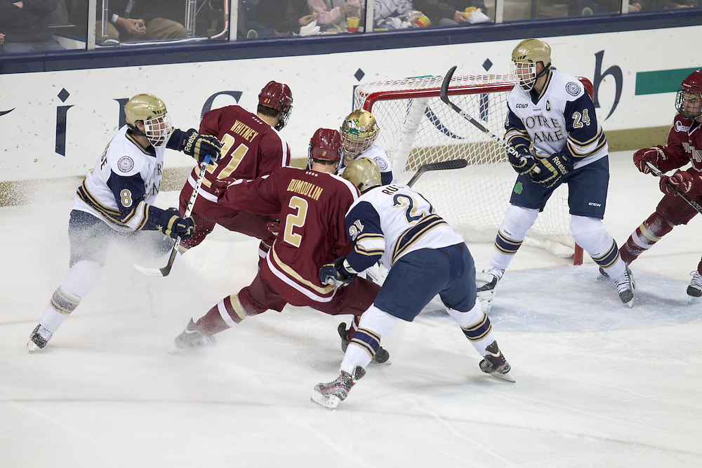 Notre Dame goaltender Mike Johnson (#32) makes save as players crash the net in action during NCAA hockey game between Notre Dame and Boston College.  The Notre Dame Fighting Irish defeated the Boston College Eagles 3-2 in game at the Compton Family Ice Arena in South Bend, Indiana.