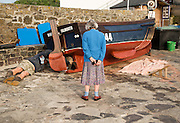Man painting small fishing boat watched by an elderly woman presumably his mother, Coverack, Cornwall, England, UK