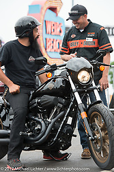 Ethan Martin of Salem, MA gets help from Randall Taylor of St Joe, MO, a fuel tank welder in the KC HD plant, before test riding a Harley-Davidson Low Rider S at the Harley-Davidson Test Ride area that recently moved to the heart of the action in Weirs Beach during Laconia Motorcycle Week, New Hampshire, USA. Friday June 16, 2017. Photography ©2017 Michael Lichter.