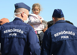 © London News Pictures. Hungarian police contain migrants close to the Hungarian and Serbian border town of Roszke, Hungary, September 7 2015. The UN's humanitarian agencies are on the verge of bankruptcy and unable to meet the basic needs of millions of people because of the size of the refugee crisis in the Middle East, Africa and Europe, senior figures within the UN have told the media.   Picture by Paul Hackett /LNP