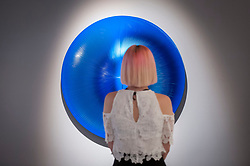 """© Licensed to London News Pictures. 28/06/2018. LONDON, UK. A visitor poses against """"Dinamica celeste e blu"""", 2006, by Alberto Biasi.  Members of the public visit Masterpiece London, the world's leading cross-collecting art fair held in the grounds of the Royal Hospital Chelsea.  The fair brings together 160 international exhibitors presenting works from antiquity to the present day and runs 28 June to 4 July 2018.  Photo credit: Stephen Chung/LNP"""