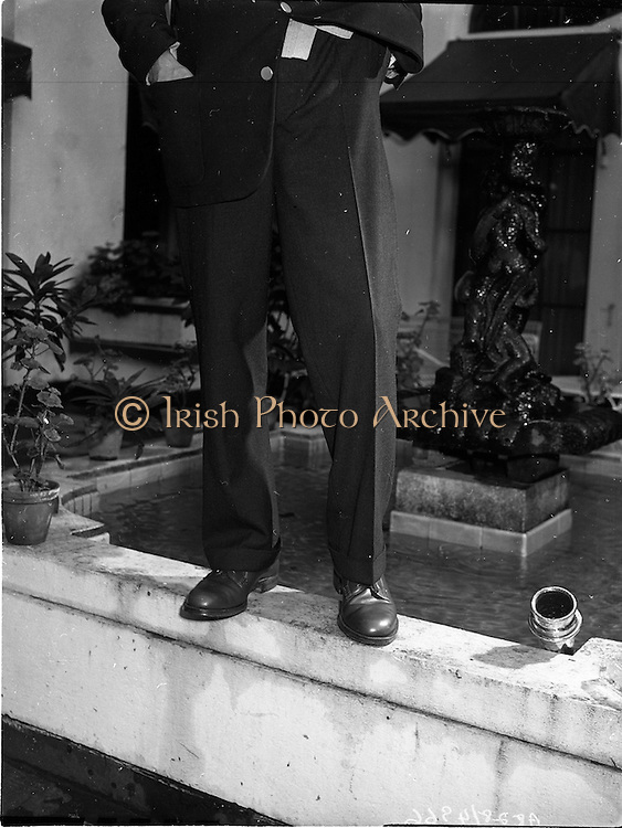 25/09/1958<br /> 09/25/1958<br /> 25 September 1958<br /> Dubtex - Prescott Reception. at the Gresham Hotel, Dublin. Image shows a demonstration of the water resistant or quick drying properties of trousers from Dubtex by having Jimmy O'Dea and a fireman spray it with a fireman's hose. <br /> Dubtex (Clothing) Ltd (Dublin Bespoke Clothing Ltd.) was based originally at 22 Wellington Quayo and had a factory called Dubtex House in Dolphins Barn, Dublin.