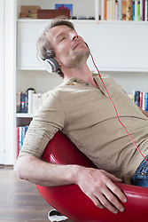 Man sitting on chair with headset and listening music