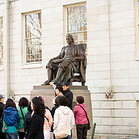 """Tourists surround the statue in Harvard Yard. Touching his foot was supposed to bring good luck. The statue has earned the nickname """"the statue of three lies"""" from its inscription, """"John Harvard, Founder, 1638"""". In truth, the statue is not modeled after John Harvard, he did not found the university, and the founding was in 1636"""
