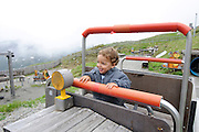 Young boy of two plays on a wooden train. Photographed in Austria