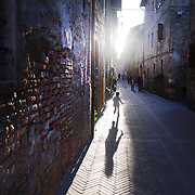 "PITIGLIANO, ITALY - OCTOBER 23: A young girl runs down one of the narrow streets in Pitigliano, a small village located in Tuscany halfway from Florence and Rome, perched atop a volcanic tufa ridge. Its unmistakable skyline makes it stand out. Pitigliano is a truly unique village in southern Tuscany, in the less-known Maremma district. The town is dubbed ""la citta' di tufo"" for the rock that it not only is built on.<br /> The village is also called ""Little Jerusalem"", not just because it looks ancient and bears a resemblance to that city, but also for the long presence of a Jewish community in the town. Pitigliano, Tuscany, Italy. 23rd October 2017. Photo by Tim Clayton/Corbis via Getty Images)"
