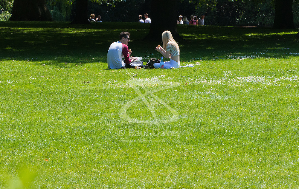 St James's Park, London, June 6th 2016. A couple enjoy a picnic in St James's Park as London basks in glorious summer sunshine with highs of 24º expected.