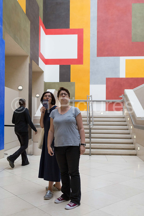 Two women read a wall caption with a background of geometric lines, right-angles and rectangles, on 4th August 2019, at Tate Britain, Millbank, London, England.