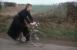 Vicar riding bicycle along country road,
