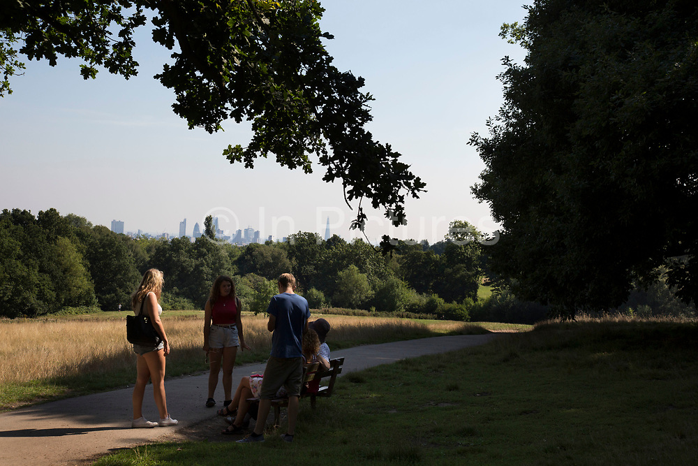 """Friends chatting with a view of the City of London behind them. Hampstead Heath (locally known as """"the Heath"""") is a large, ancient London park, covering 320 hectares (790acres). This grassy public space is one of the highest points in London, running from Hampstead to Highgate. The Heath is rambling and hilly, embracing ponds, recent and ancient woodlands."""