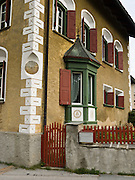 """A house built in 1564 shows characteristic architecture in Baselgia, Upper Engadine, Switzerland, the Alps, Europe. Sgraffito (or scraffito, plural: sgraffiti) is a technique of wall decor where layers of plaster tinted in contrasting colors are applied to a moistened surface. The Swiss valley of Engadine translates as the """"garden of the En (or Inn) River"""" (Engadin in German, Engiadina in Romansh, Engadina in Italian)."""