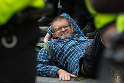 An environmental activist from Extinction Rebellion lies glued to the road after a vintage bus was used to block a junction to the south of London Bridge on the ninth day of their Impossible Rebellion protests on 31st August 2021 in London, United Kingdom. Extinction Rebellion are calling on the UK government to cease all new fossil fuel investment with immediate effect.