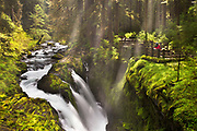 Photographer stands above Sol Duc Falls in Washington's Olympic National Park.