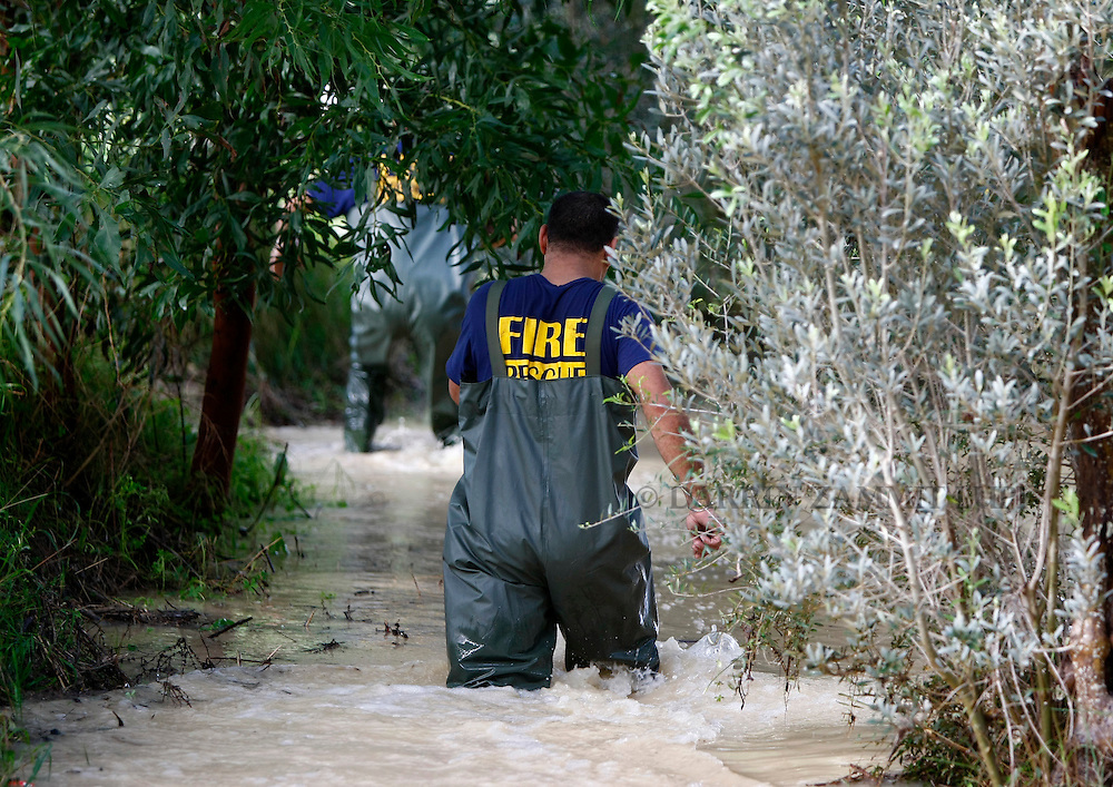 Civil Protection officers wade through a flooded field while making their way towards a suspected stranded car at Kennedy Grove near St Paul's Bay in the north of Malta October 25, 2010.  An overnight storm dumped 87.3mm of rainfall on the Mediterranean island, causing some damage but no casualties, according to government officials...REUTERS/Darrin Zammit Lupi (MALTA)