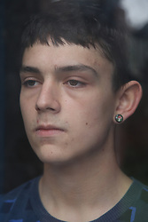 Teenage boy looking out of window