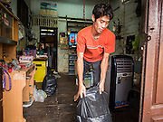 14 SEPTEMBER 2015 - BANGKOK, THAILAND:  A man takes some of his belongings out of the home he's being evicted from. Fiftyfour homes around Wat Kalayanamit, a historic Buddhist temple on the Chao Phraya River in the Thonburi section of Bangkok are being razed and the residents evicted to make way for new development at the temple. The abbot of the temple said he was evicting the residents, who have lived on the temple grounds for generations, because their homes are unsafe and because he wants to improve the temple grounds. The evictions are a part of a Bangkok trend, especially along the Chao Phraya River and BTS light rail lines. Low income people are being evicted from their long time homes to make way for urban renewal.           PHOTO BY JACK KURTZ