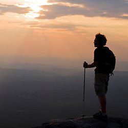 A man watches the sunset on the summit of Mount Monadnock in Monadnock State Park in Jaffrey, New Hampshire.