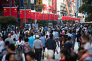 Pedestrians walk past Chinese national flags displayed along the Nanjing Road pedestrian street in Shanghai, China, on Friday, Oct. 2, 2015.