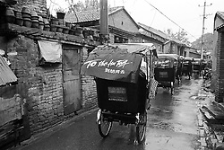 Tourists in bicycle rickshaws touring old hutong streets in Beijing China