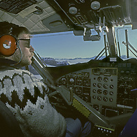 ANTARCTICA, Twin Otter ski plane pilot Henry Perk flies in Ellsworth Mountains. Sun compass on right was used for navigation before GPS was publically available.